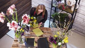 Florist in own flower shop, preparing bouquets stock footage