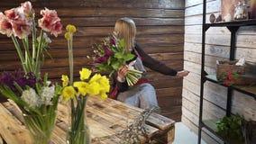 Florist in own flower shop, preparing bouquets stock video footage