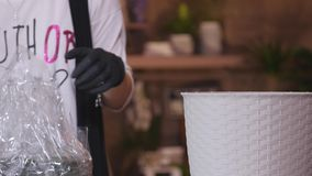 Florist in own flower shop, preparing a pot for a bouquet. close up stock video footage