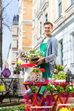 Florist with plant supply at shop. Young handsome florist delivering palette of flowers or viola Royalty Free Stock Photography