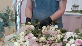 Florist prepares a bouquet of flowers for sale stock video footage