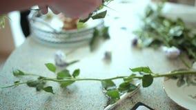 Florist prepares flowers for a floral composition. Florist prepares flowers for a floral bouquet composition stock footage