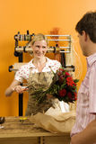 Florist preparing bouquet of red flowers for male customer behind counter in flower shop, smiling Stock Image