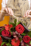 Florist preparing bouquet of red flowers, tying knot with string, close-up, mid-section Royalty Free Stock Images
