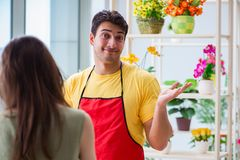 The florist selling flowers in a flower shop Royalty Free Stock Images