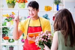 The florist selling flowers in a flower shop Royalty Free Stock Image