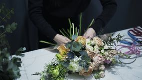 Florist shop assistant matching a ribbon to a bunch of flowers. Unrecognizable woman in black clothes working in a florist shop matching a ribbon color to a stock footage