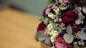 Florist shows finished flower arrangement on table inside office stock video