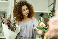 Curly blue-eyed florist smiling while meeting clients in her floral shop. Florist smiling. Curly blue-eyed pleasant beautiful florist smiling broadly while stock photography