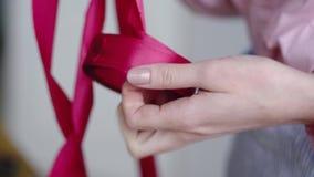Florist takes a ribbon in a flower shop to arrange a bouquet. 4k stock video