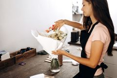 Florist touches bouquet of flowers in pastel colors packed in white paper is in a vase. stock images
