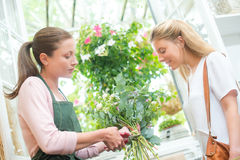 Florist trimming stems flowers for customer Stock Photography