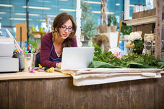 Florist Using Laptop At Counter In Flower Shop Stock Photo