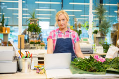 Florist Using Laptop At Counter In Flower Shop Royalty Free Stock Image