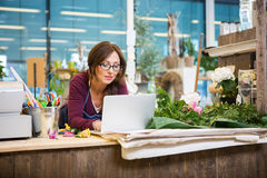 Florist Using Laptop In Flower Shop Royalty Free Stock Photos