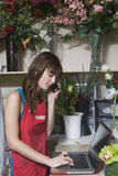 Florist Using Laptop And Mobile Phone In Shop Royalty Free Stock Image