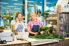Florist Using Mobile Phone While Colleague Making Royalty Free Stock Photo