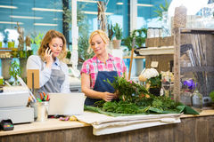Florist Using Mobile Phone While Colleague Making Royalty Free Stock Photography