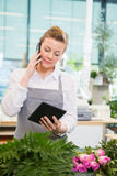 Florist Using Mobile Phone And Digital Tablet In Stock Images