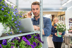 Florist Using Mobile Phone And Laptop In Shop Stock Image