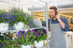 Florist Using Mobile Phone And Laptop In Shop. Male florist using mobile phone and laptop in flower shop Royalty Free Stock Photo