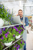 Florist Using Mobile Phone And Laptop In Shop Royalty Free Stock Image