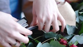 Florist using stapler to attach a craft paper. Close up view of arranging bouquet. 4k royalty free stock photo
