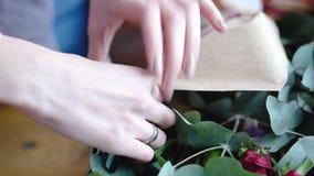 Florist using stapler to attach a craft paper. Close up view of arranging bouquet. 4k stock video
