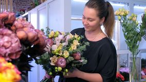 Florist woman makes big flower bouquet and smiles look at camera in flower shop. stock video
