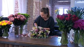 Florist woman makes big flower bouquet and ties stems of ribbon in flower shop.
