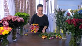 Florist woman makes bouquet from small colourful roses works in flower shop. stock footage