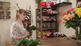 Florist woman is making decor from multicolored garden flowers in a shop stock video footage