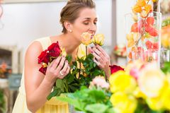 Florist woman smelling at roses. Enjoying the scent stock images