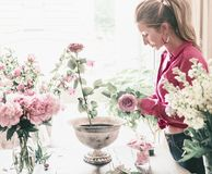 Florist women with long blond hair make beautiful big festive event classical bouquet with roses and other flowers in urn vase stock images