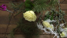 Florist at work arranging flowers into a bouquet. stock video footage