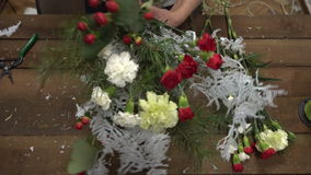 Florist at work arranging flowers into a bouquet. stock video
