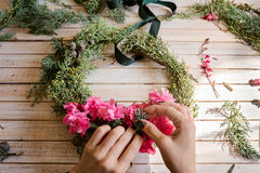 Florist at work: Creating a wooden wreath with flowers. christma Stock Photo