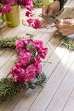 Florist at work: Creating a wooden wreath with flowers. christma Stock Image