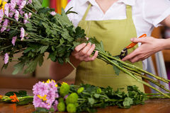 Florist at work. Cropped image of female florist in apron cutting flowers Stock Photos