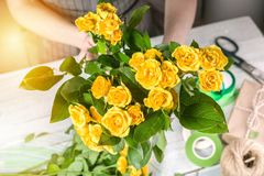Florist at work. Female hands collect a wedding bouquet of roses. People in the process of work. Female hands collect a wedding bouquet of roses. People in the royalty free stock image