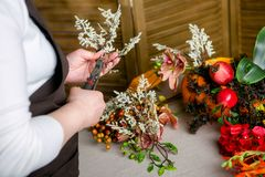 Florist at work: How to make a Thanksgiving centerpiece with big pumpkin and bouquet of flowers. Step by step, tutorial. royalty free stock image