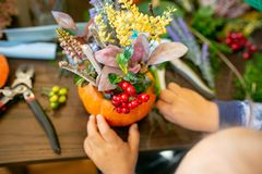 How to make a Thanksgiving centerpiece with big pumpkin and bouquet of flowers. stock photo