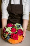Florist at work: How to make a Thanksgiving centerpiece with big pumpkin and bouquet of flowers. Step by step, tutorial. stock image
