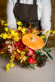 Florist at work: How to make a Thanksgiving centerpiece with big pumpkin and bouquet of flowers. Step by step, tutorial. royalty free stock photo