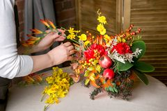 Florist at work: How to make a Thanksgiving centerpiece with big pumpkin and bouquet of flowers. Step by step, tutorial. stock photography