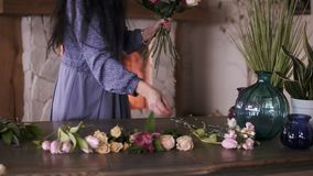 Florist at work: pretty brunette adult woman making fashion modern bouquet of different flowers and plants at home. Studio. Side view stock video
