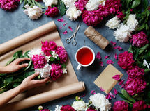 Florist at work: pretty woman making summer bouquet of peonies on a working gray desk. Kraft paper, scissors, string Royalty Free Stock Photos