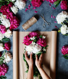 Florist at work: pretty woman making summer bouquet of peonies on a working gray desk. Kraft paper, scissors on the Stock Images