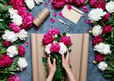 Florist at work: pretty woman making summer bouquet of peonies on a working gray table. Kraft paper, scissors, envelope Stock Photos