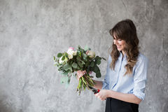 Florist at work: pretty young woman making fashion modern bouquet of different flowers Royalty Free Stock Photo